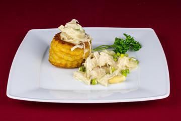 Hühnerfrikassee mit Pastete auf einem Teller serviert mit Spargel und Erbsen garniert mit Petersilie