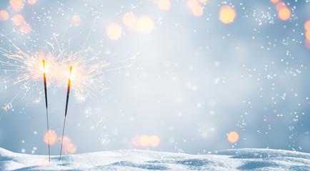 zwei brennende wunderkerzen im schnee