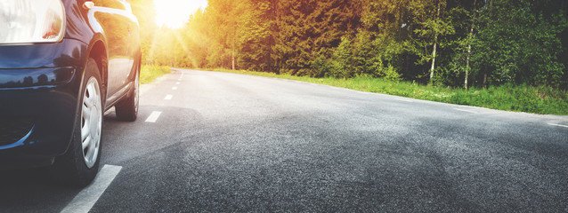 Wall Mural - Car on asphalt road on summer day at park. Transportation panoramic background with sunlight