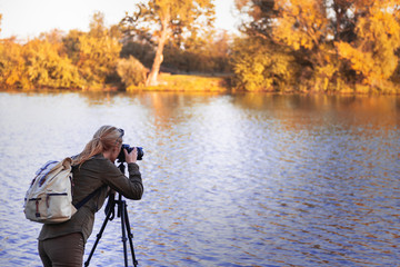 Woman is taking picture of landscape at autumn. Hiker with camera on tripod standing next to lake.