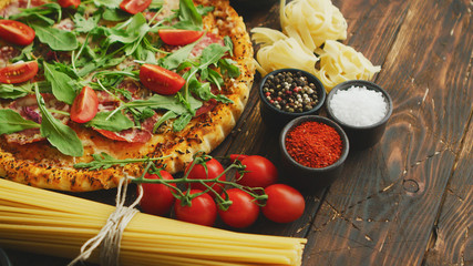 Italian food background with pizza, raw pasta, spices, herbs, wine, and vegetables on wooden table