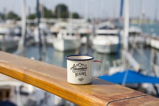 An aluminum enamel mug for a hike on a wooden table on the board of the yacht in the port of Italy among other yachts on a sunny summer day.