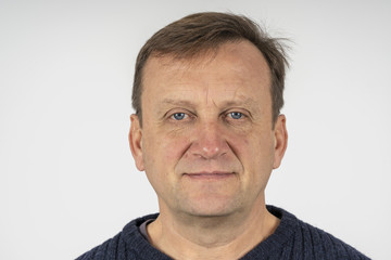 Portrait of a middle-aged man against a white wall background