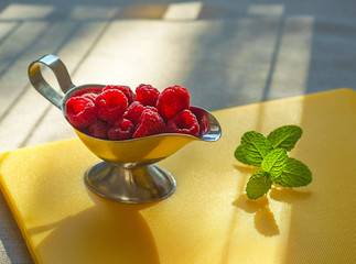 Ripe sweet raspberries in silver bowl and mint on yellow kitchen board in lights of sun. Close up, healthy breakfast ingredient, top view
