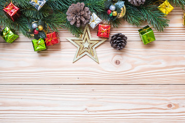 Christmas background with decoration, gift box, Star shape, Bell and pine tree branches on wooden board, Happy New Year and Xmas Holidays banner. Top view and Copy Space for your text