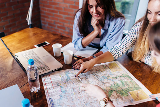 Smiling female friends sitting at desk planning their vacation looking for destinations on map