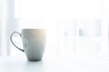 Coffee cup on white table in the morning and sunlight