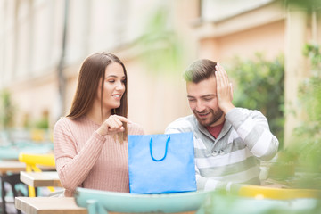 Young couple with shopping bag sitting outdoors