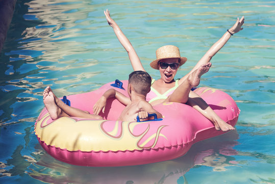 Mother and son enjoying their holidays in waterpark. They are swimming in a rubber ring along the lazy river, smiling, having fun, their hands are up.