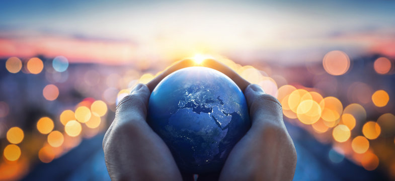 The globe Earth in the hands of man against the night city. Concept on business, politics, ecology and media. Earth day abstract background. Elements of this image furnished by NASA