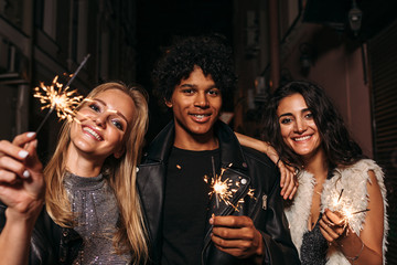 Group of friends standing on sidewalk at night, holding sparklers