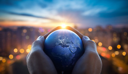 The globe Earth in the hands of man against the night city. Concept on business, politics, ecology and media. Earth day abstract background. Elements of this image furnished by NASA. Wall mural
