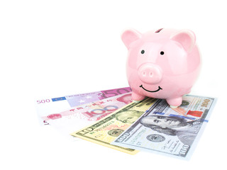 Pink piggy bank on dollars, chinese, euro banknote isolated on white background, saving concept