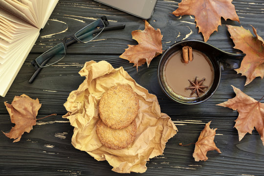 Autumn composition. Cup of coffee, lemon cookies, open book, eyeglasses, maple leaves on black wooden background with copy space, top view.