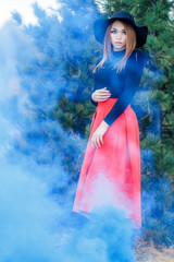 Woman in a cloud of bright blue smoke