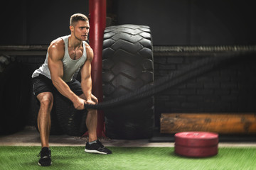 Man is making battle rope exercises during his cross training workout