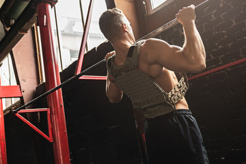 Strong man doing pull up exercise in the gym