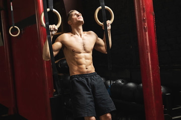 Sportsman doing muscle ups exercise on the  gymnastic rings.