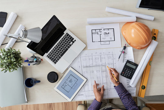 Construction engineer working with various blueprints on his table, view from above