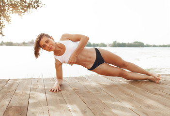 beautiful athletic girl with a short haircut do sports exercise in a plank pose near the lake in summer