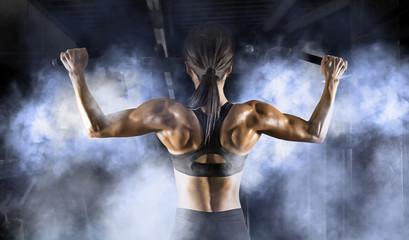 Muscular woman. Back training