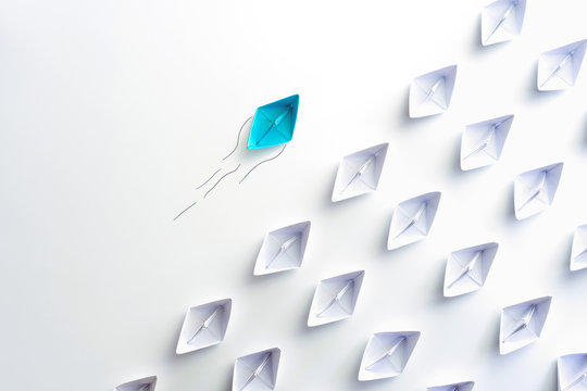 Blue paper ship are different from others and group of paper ships in one direction. Business for Innovative, solution concepts.