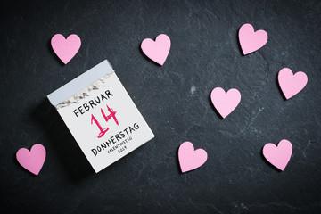Abreißkalender mit Valentinstag 2019 und dekorativen Herzen auf Schieferuntergrund