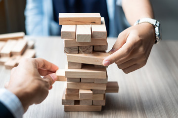 Businessman and Businesswoman hand placing or pulling wooden block on the tower. Business planning, Risk Management, Solution, strategy , Partnership and Cooperation Concepts Wall mural