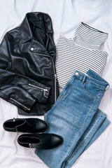 Set of casual female clothes: leather black biker jacket, striped turtleneck , blue skinny jeans, leather ankle boots on white background. Top view.
