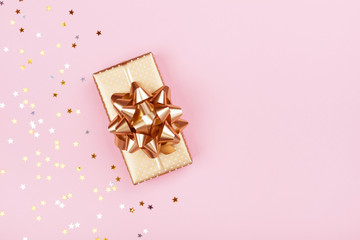 Golden gift or present box and stars confetti on pink background top view. Flat lay composition for birthday, christmas or wedding.