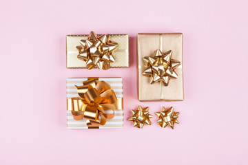 Gifts or presents boxes with golden bows on pink pastel background top view. Flat lay composition for birthday, christmas or wedding.