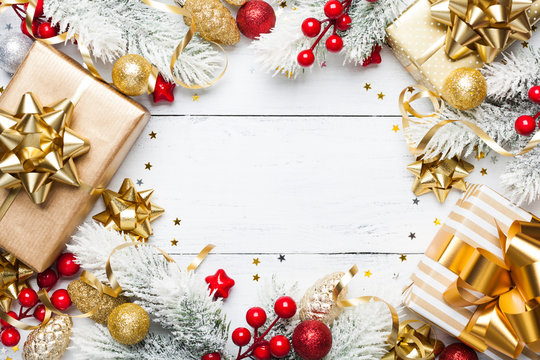Golden gifts or presents boxes, snowy fir tree and christmas decorations on white wooden table top view. Flat lay.