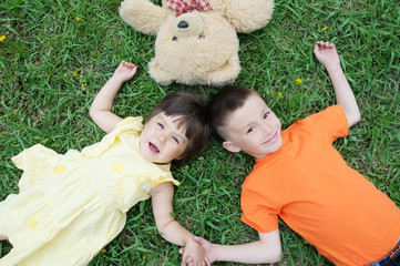 Top view of kids lying on the grass at park having fun. Little girl and boy relax with smiling. Teddy bear toy together