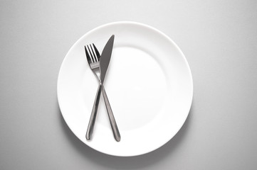 metal knife and fork on clean white plate for restaurant or food meal serving with grey background