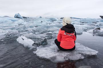 Mujer joven sentada en laguna glaciar en Islandia.