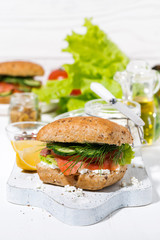 sandwich with salted fish, fresh vegetebles and cream cheese on wooden board, vertical