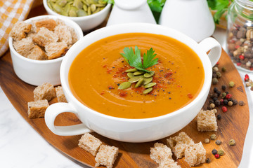 soup of pumpkin and lentils and ingredients on wooden board, closeup
