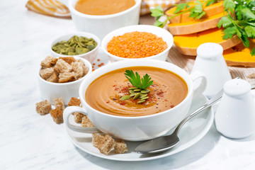 soup of pumpkin and lentils in a bowl on white background