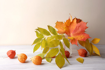 Maple and ash tree leaves in vase in interior. Autumn colorful composition as decoration indoor.