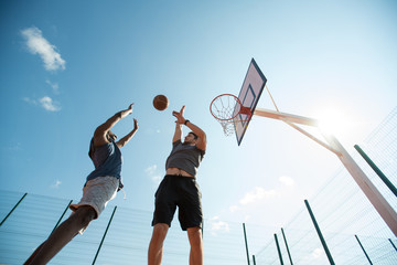 Low angle  of two young men playing basketball and jumping by hoop against blue sky, copy space