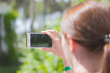 Woman using mobile phone to take photo