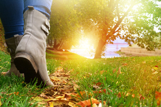 Woman in grey shoes and jeans walking on the autumn forest path with yellow leaves