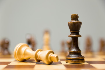 Two King chess pieces on a chessboard with the light king lying on its side at the foot of the victorious dark wood King