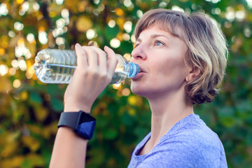 Portrait of happy fitness woman drinking water after workout outdoors. Diet, healthcare and sport concept.
