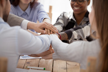 Close up group of young millennial business people or students stacking their hands palm, sitting in office at work. Gesture sign of support unity and togetherness, starting common business concept