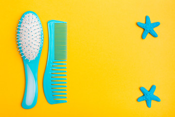 A set of plastic combs and two hairpins in the shape of a starfish on a yellow background. Top view