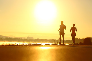Man and woman silhouettes running at sunrise