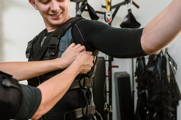 Woman fastening electro muscular stimulation vest on man