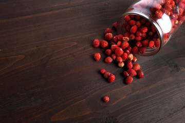 Strawberries scattered on a dark wooden background. Copyspace on the left.