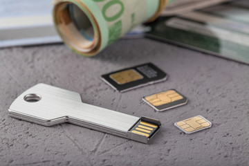 Three SIM cards of different sizes lie on a rough surface. Close-up.